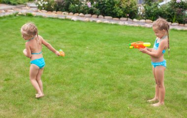 Two little adorable girls playing with water guns in the yard