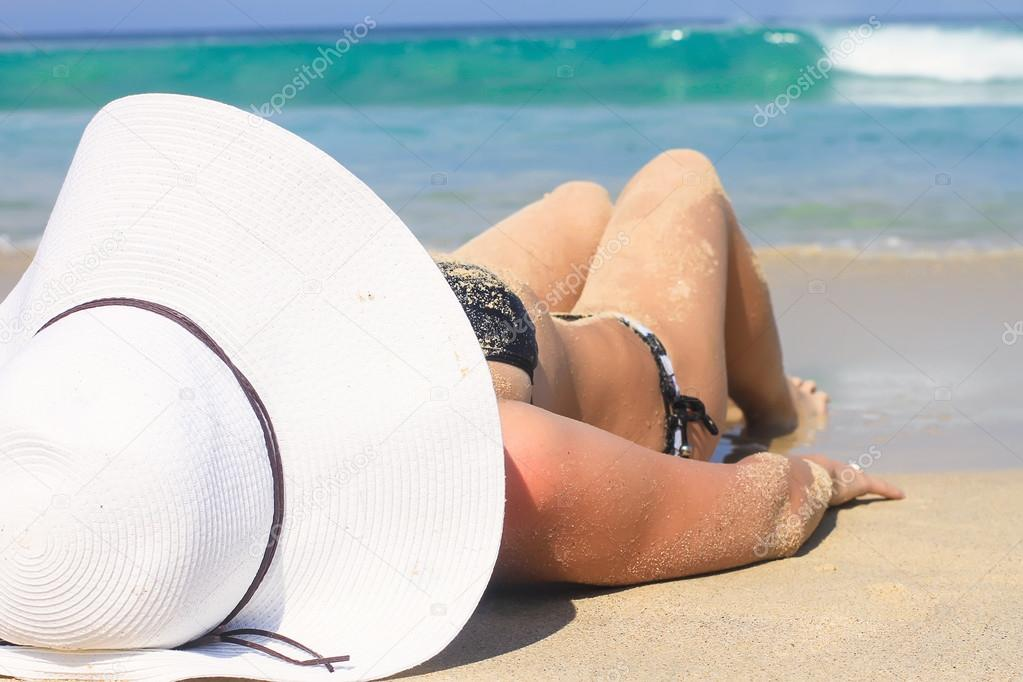 Young woman in white hat enjoying summer vacation on tropical beach