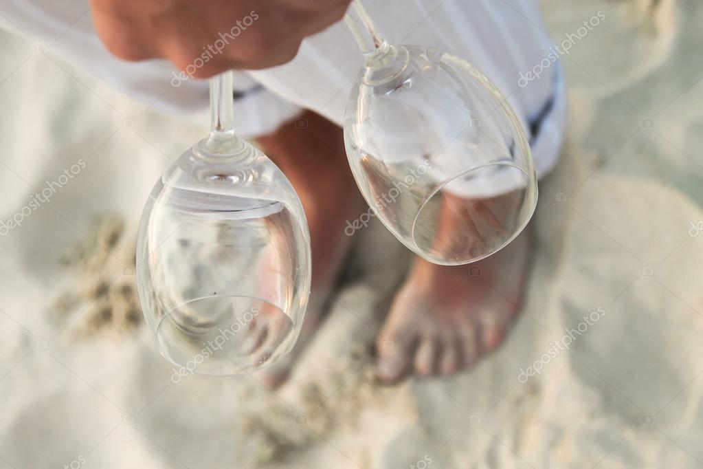 Closeup of two glasses in hand at man walking barefoot on the beach