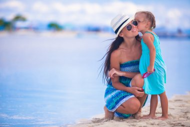 Little girl kissing her mother on a white, tropical beach