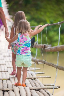 Back view of little girls walking on suspension bridge over the River Loboc, Philippines