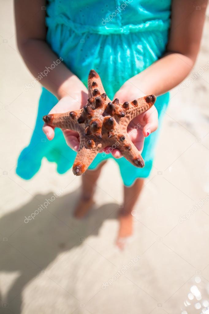 Kid's hands holding starfish