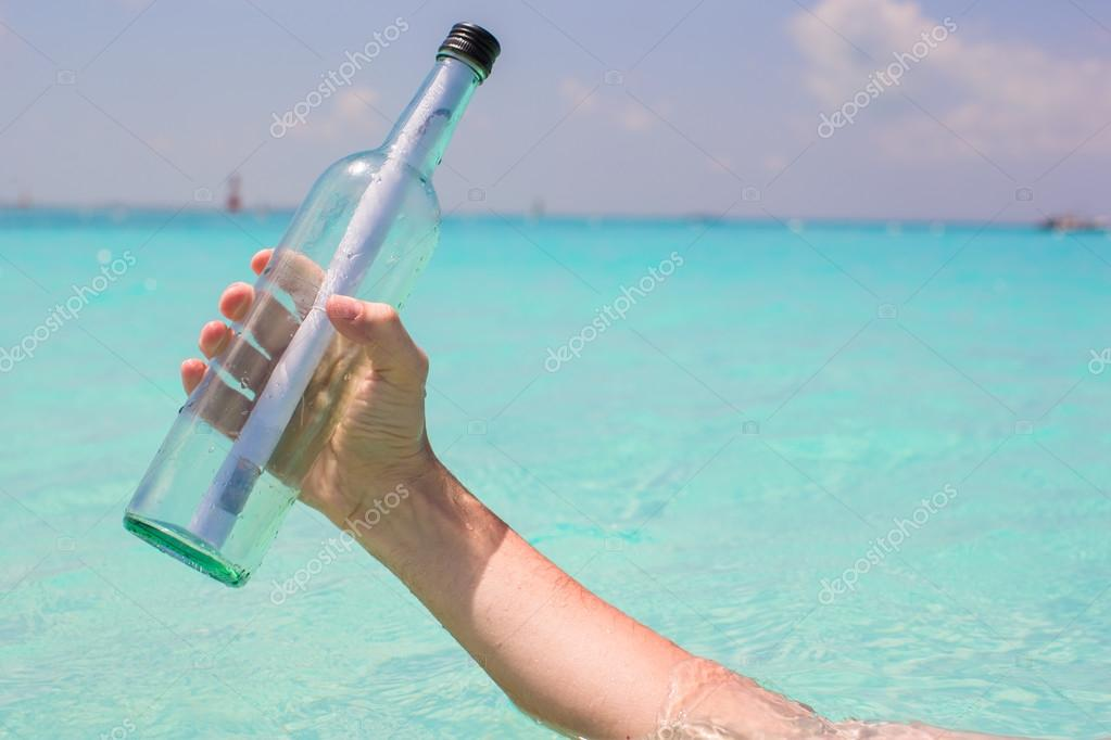 Bottle with a message in the hand background blue sky