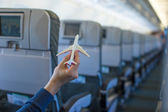 大型航空機の中の飛行機モデルを持っている手を閉じる