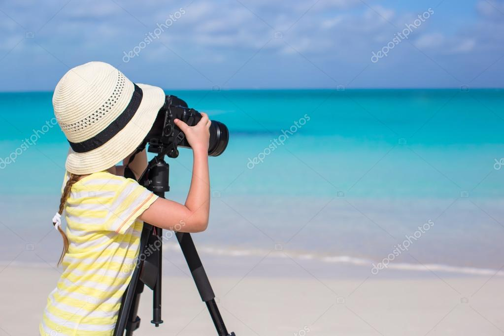 Little girl with camera on a tripod at white sandy beach