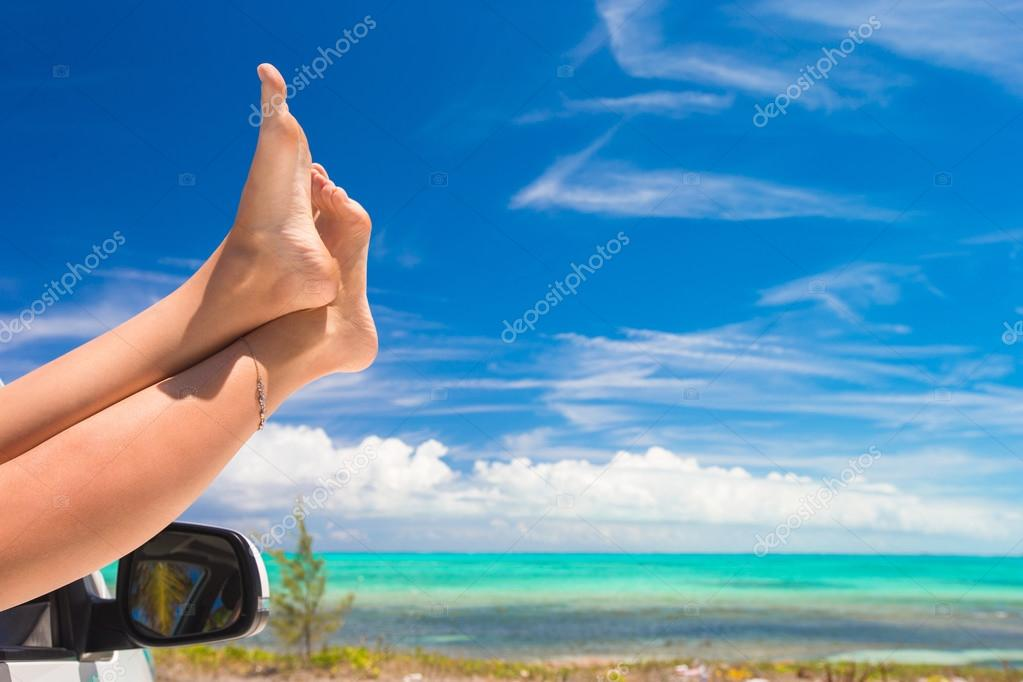 Female barefoot from the window of a car on background tropical beach