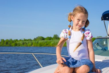 Little girl sailing on a luxury yacht