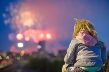 Rear view of little girl against a beautiful fireworks