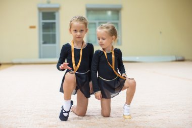 Two little gymnasts in the gym with medals