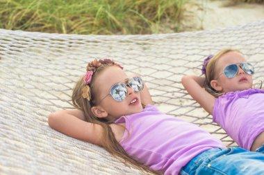 Little cute girls relaxing in hammock on summer vacation