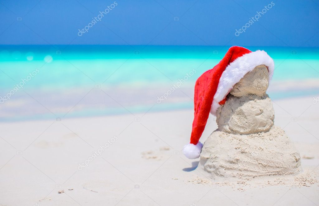 Little sandy snowman with red Santa Hat on white Caribbean beach