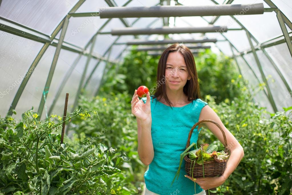 young woman holding a basket of greenery and tomatos in the greenhouse