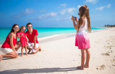 Little girl making photo on phone of her family at the beach