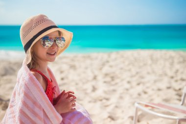 Cute little girl in hat on beach during summer vacation