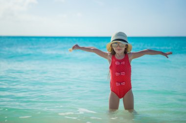 Adorable little girl in hat on beach during summer vacation