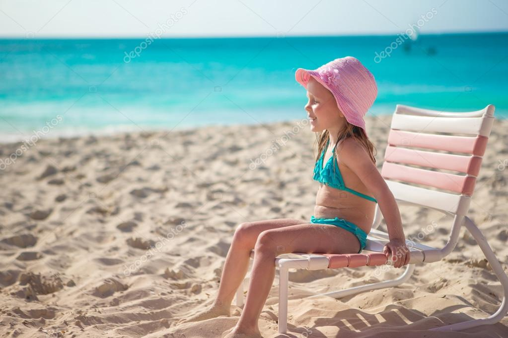 Adorable little girl in hat at beach during caribbean vacation