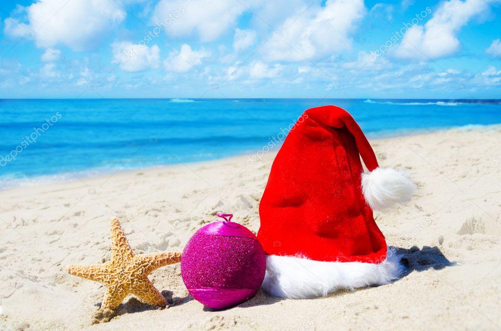 Christmas hat with christmas ball and starfish on the beach