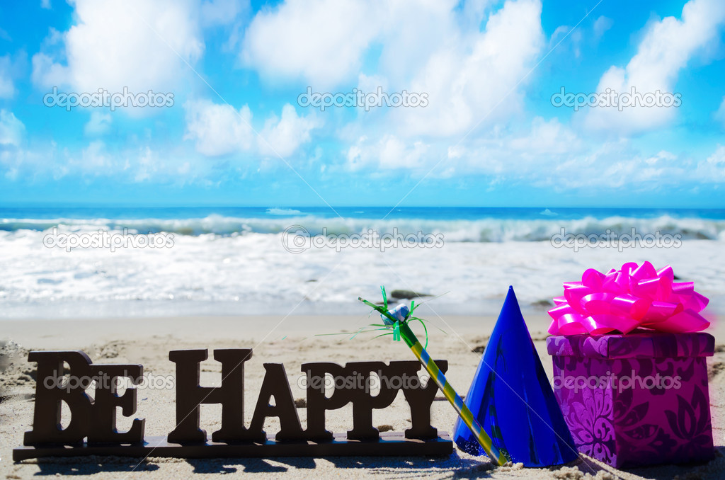 Sign Be Happy with Birthday decorations on the beach Stock