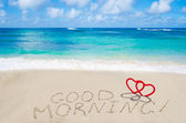 Sign Good morning with hearts on the beach