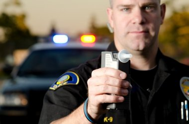 A police officer holds a breath test machine