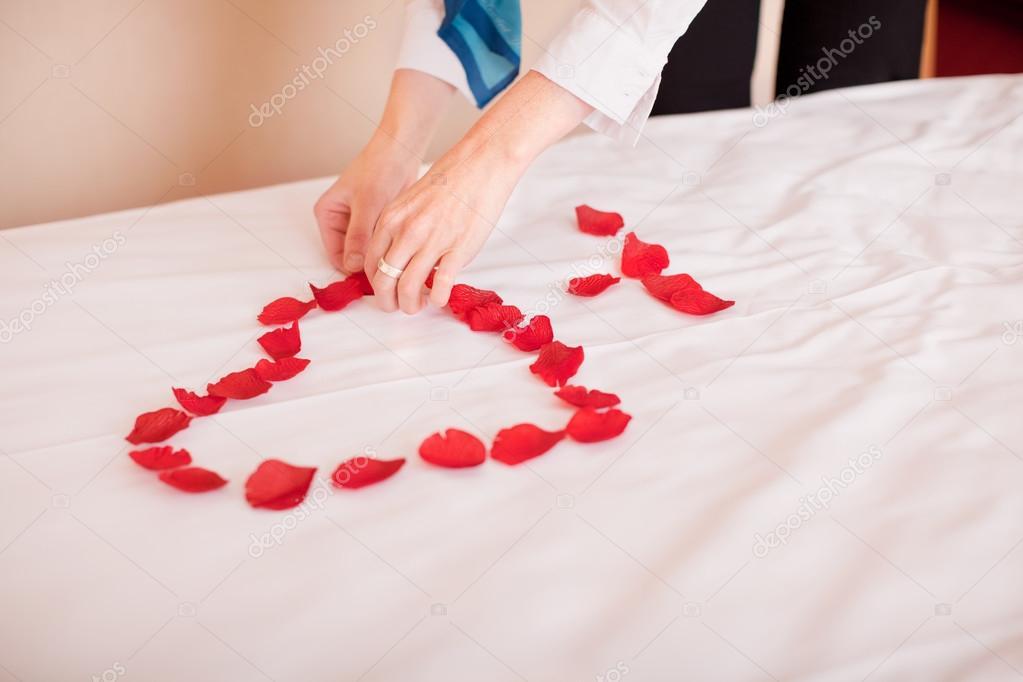 mani petali a forma di cuore sul letto — Foto Stock © racorn #26182755
