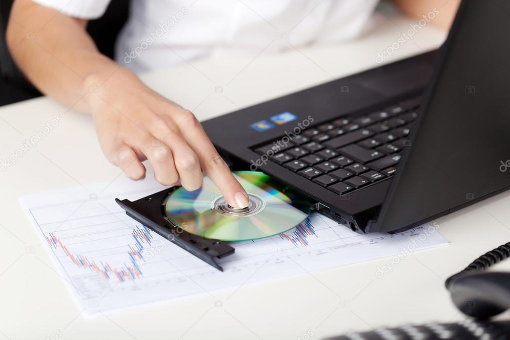 woman putting a cd in her laptop stock photo racorn 26440213