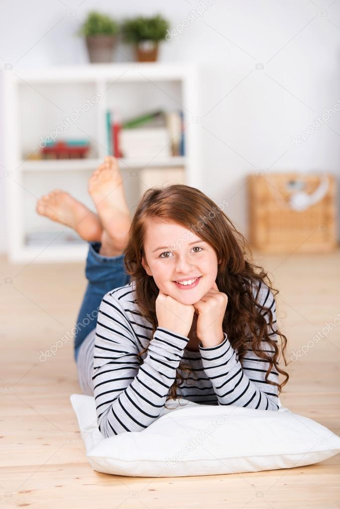 Lächelndes junges Teenager-Mädchen auf dem Boden liegend