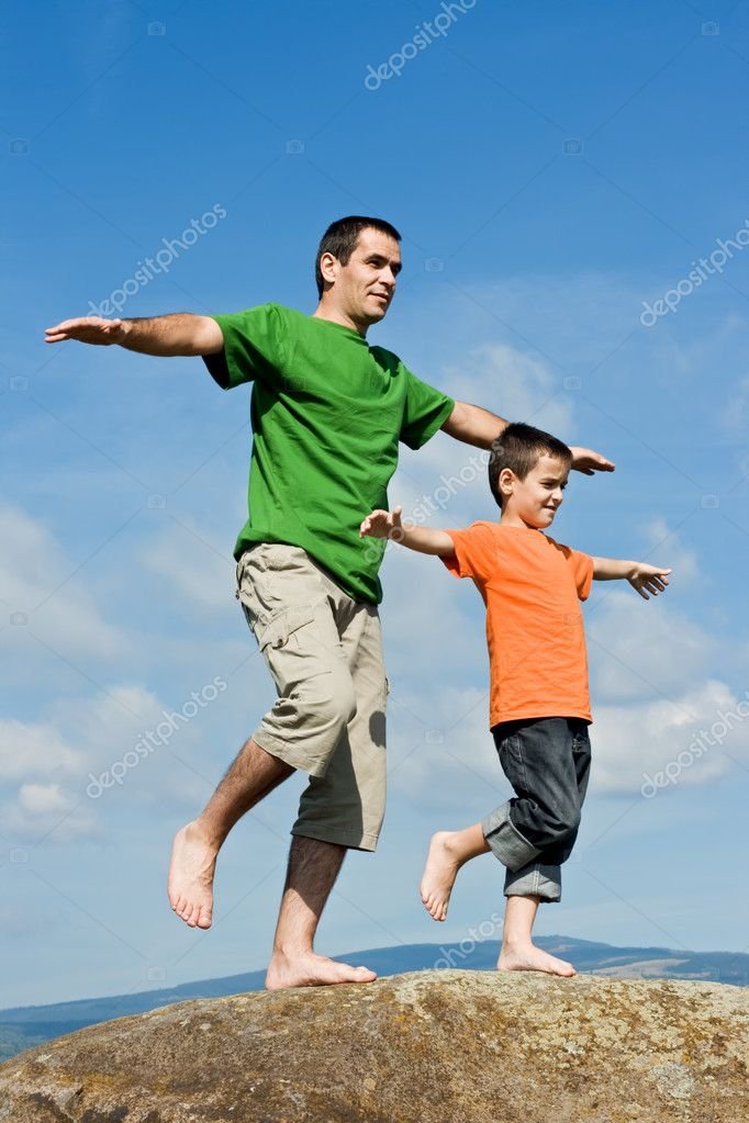 Father and his son staying on the stone