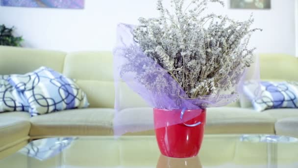 Vase of lavender flower on the table in living room, with sofa in background. Lavender as room decoration and fragrance