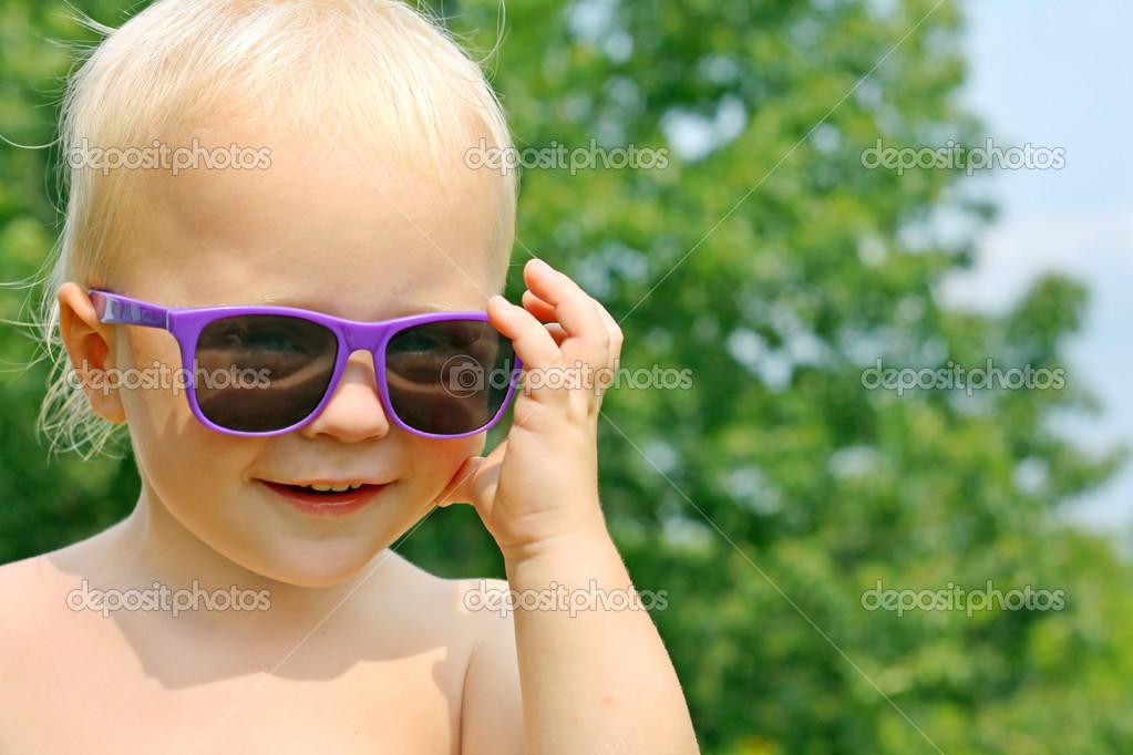c13825d007 ... χαρούμενος αγοράκι φοράει μωβ γυαλιά ηλίου και χαμογελαστός όπως  κοιτάζει την κάμερα έξω σε μια ηλιόλουστη καλοκαιρινή μέρα — Εικόνα από ...