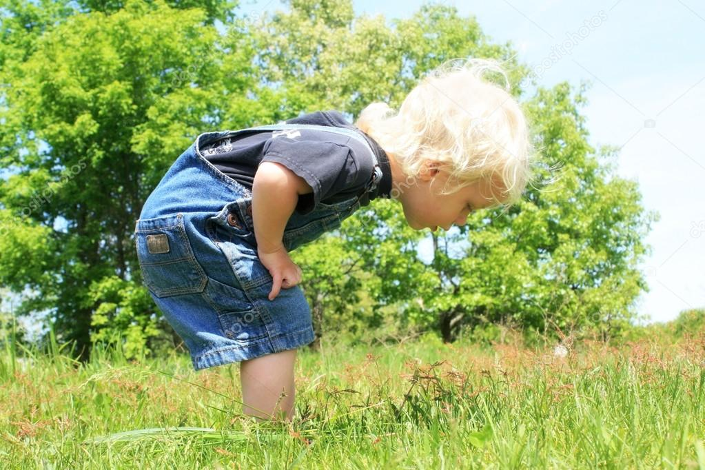 Little Boy looking at Somehing in the Grass