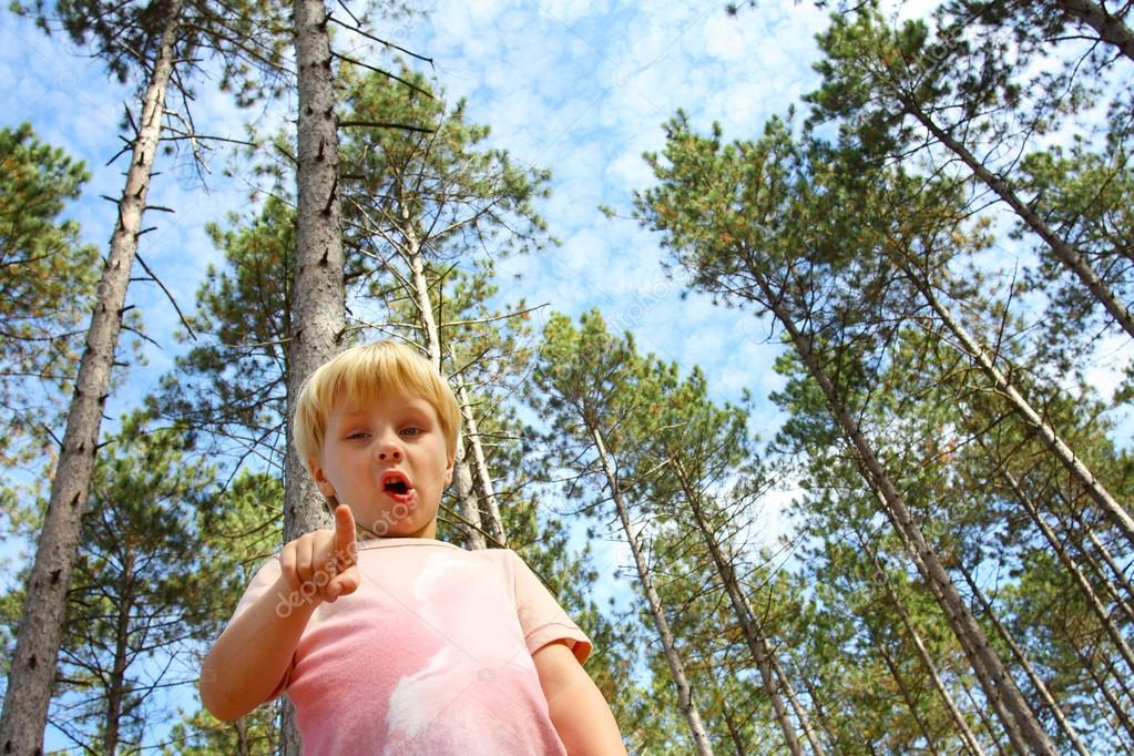 Young Child in Forest Pointing at Camera