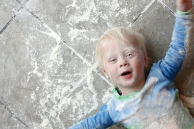 Messy Baby Covered in Baking Flour