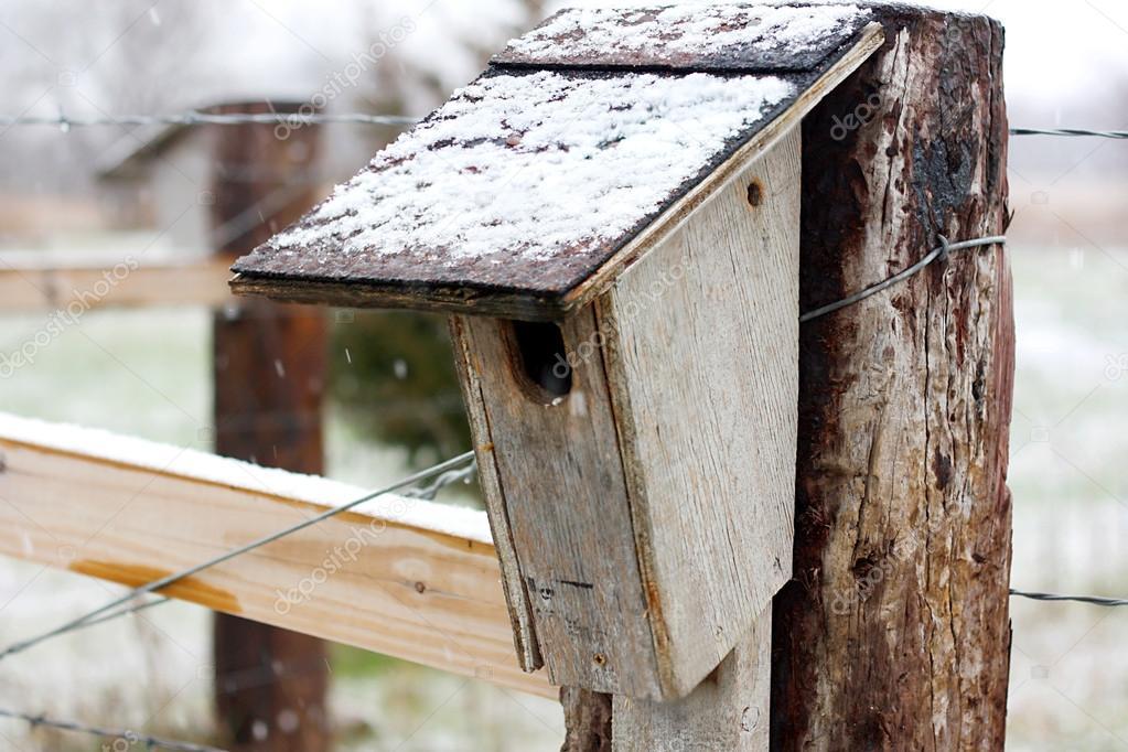 Old Homemade Birdhouse on Farm Fence in Snow