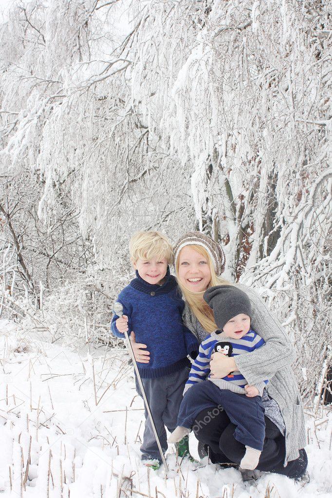 Mother and Two Children in Winter Wonderland