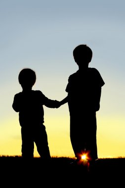 Silhouette Young Children Holding Hands at Sunset