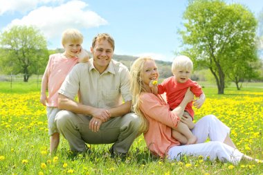 Happy Familly of Four People Relaxing in Flower Meadow