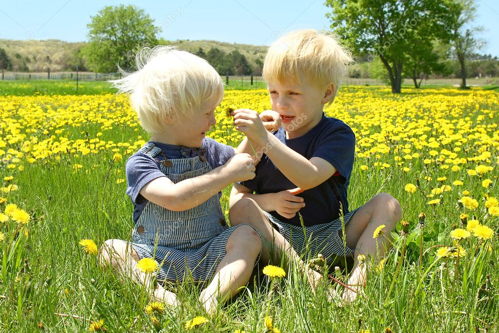 Two Children Playing Outside and Smelling Flowers