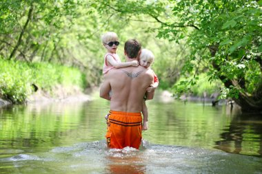 Father and Young Children Walking in River in Forest