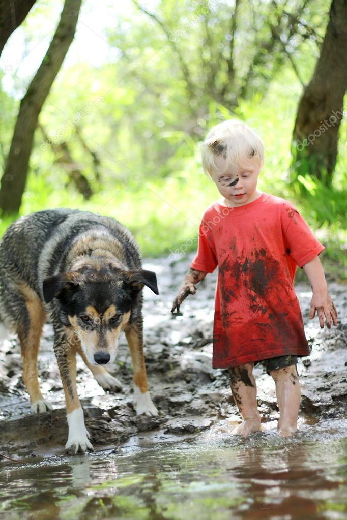 Young Child and Dog Playing in Muddy River