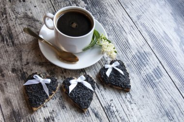 Three wedding cookies decorated black sesame with a cup of coffee. Retro style.