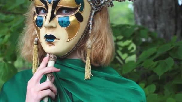 krásná žena v karnevalové masce listoví pozadí