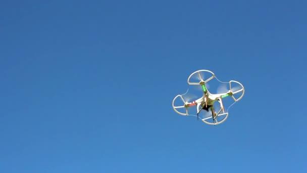 quadrocopter přelétají nad nimi proti modré obloze