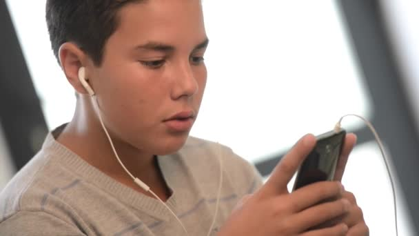 Mladý teenager leží na pohovce, poslech hudby na svůj telefon