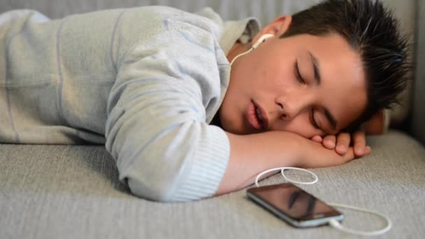 Young teenager lying on a sofa listening to music on his phone