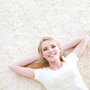Beautiful blond woman posing lying down on a carpet.