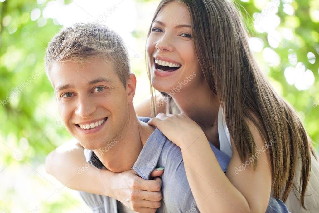 Portrait of a smiling young couple in an outdoor setting.