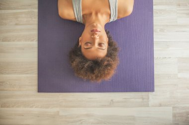 African Woman Lying on a Yoga Mat