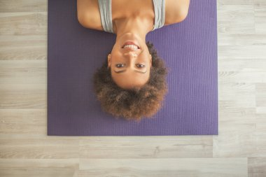 Smiling African Woman Lying on the Yoga Mat