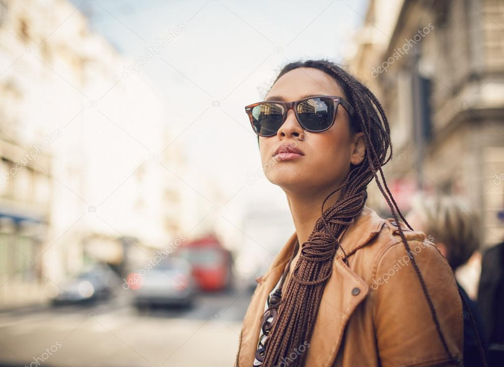 Portrait of a young African woman wearing sunglasses outdoors.